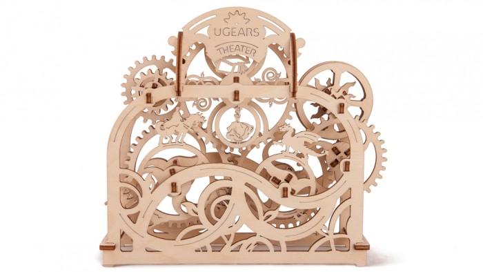 Конструктор Ugears 3D-Пазл Театр 70 деталей3D-Пазл Театр 70 деталейКонструктор 3D-Пазл Ugears Театр  Механический театр от UGears – это деревянный конструктор с множеством движущихся деталей, 3D-пазл, кинетическая скульптура, игра и настольный вертеп одновременно. Это вещь со смыслом. Механический театр позволит вам и вашим детям разобраться в устройстве волшебной сказки. Познавая её внутренние механизмы, вы научитесь составлять собственные истории.  На шестерне протагонистов выстроен замок, а живут на ней Принц и Король. В их вечном поиске им пытаются помешать обитающие на другом колесе огнедышащий Дракон, злая Ведьма и хитрый Шут. Добро всегда вознаграждается за победу над злом, потому на третьем колесе – колесе выбора наград – вращаются Сундук с драгоценностями и Принцесса. Крутите приводное колесо и смотрите, как сменяются места, герои, их противники и награды, а над миром бесконечно крутится солнечная шестерня.  Любой театр – это, прежде всего, игра, а благодаря приложенным правилам вы сможете поиграть в Механический театр на очки. Развлеките необычной забавой гостя, ребёнка или любимого человека.  Дизайн  Дизайнеры создали настоящий механический вертеп. Модель оформлена растительными мотивами, которые заполняют избытки пустого пространства и создают атмосферу. Сцена разделена на три больших зоны: на холме стоит один из протагонистов, добрых главных героев, впадина напротив отведена антагонистам, а над всеми ними вращается колесо с достойной наградой победителю. Справа вверху от персонажей то ли заходя, то ли поднимаясь над горизонтом, в небесах крутится солнечная шестерня. S-образная планка, проходящая посередине «кадра» и поддерживающая шестерни, также выполняет роль ландшафта.  Модель изготовлена на лазерном станке, потому вероятность появления заусенцев минимальна, а торцы не будут расслаиваться благодаря тепловой обработке. Преимущества перед штампованными моделями очевидны.  Как это работает?  Выдавите детали из планшетов и соберите модель, следуя наглядн