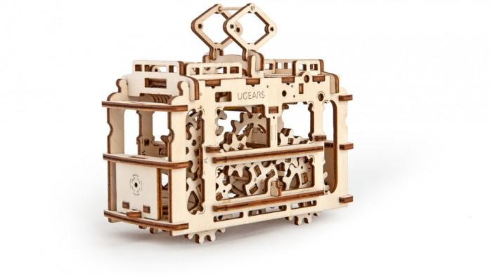 Конструктор Ugears 3D-Пазл Трамвай с рельсами 154 детали3D-Пазл Трамвай с рельсами 154 деталиКонструктор 3D-Пазл Ugears Трамвай с рельсами – это новая модель в серии механических 3D-пазлов, успешно завоевывающих умы гиков и розничные магазины игрушек. Маленький трамвайчик будет доставлять ваши посылки и письма с одного конца стола на другой.  В движение модель приводится резиномотором и ездит в обе стороны. Приподнимите специальным рычагом рельсы с одного из концов, чтобы трамвайчик медленно покатился к другому.  Дизайн Через каркас модели виден зубчатый механизм, синхронное вращение его шестерней завораживает. На крыше вы найдете потайное «багажное отделение» отделение для мелких вещей и записок.  Набор изготовлен из фанеры при помощи программируемого лазерного станка: детали легко выдавливаются из планшетов, заусенцев практически не образуется, все надписи (режимы движения, условные обозначения, логотип производителя) нанесены тоже при помощи лазера. По качеству эти модели намного превосходят изготовленные штампованием.  Как это работает? Для сборки модели вам не потребуются клей или дополнительные инструменты. Просто выдавите детали из планшетов, запаситесь зубочистками и терпением. Подвижные сочленения можно смазать восковой или стеариновой свечой.  В качестве рабочего тела мотора используется обыкновенная канцелярская резинка, которую благодаря конструкции модели легко заменить.  Характеристики Материал фанера (ФК) Размер упаковки 370 &#215; 170 &#215; 30 мм Размеры модели 158 &#215; 73 &#215; 137 мм Длина дороги 767 &#215; 54 &#215; 70 мм   Что в коробке Набор планшетов с деталями для сборки 3D-пазла Трамвай Документация (RU, UA, EN)<br>