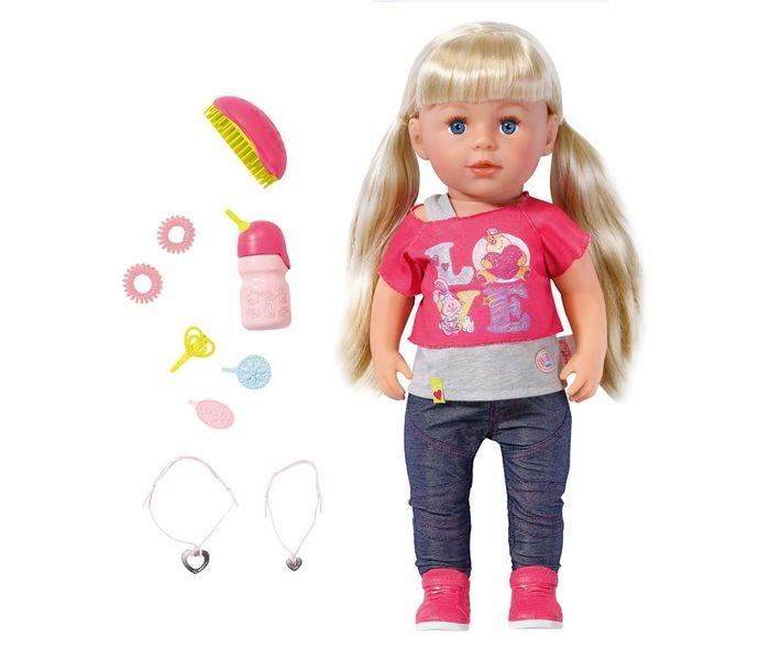 Zapf Creation Кукла Baby born Сестричка 43 см с акссесуарамиКуклы и одежда для кукол<br>Кукла Baby Born Сестричка, 43 см, кор.  Высота куклы составляет 43 см, у нее длинные белокурые волосы. У нее сгибаются в коленях ноги, она также устойчива в вертикальном положении. Кукла умеет пить из бутылочки и плакать настоящими слезами (для этого ее нужно предварительно напоить водой). Кроме того, ее можно купать!   Кукла Сестричка одета в яркий, стильный наряд: розовая футболочка с надписью Love, эффектные синие брюки и розовые кроссовки. В комплект также входят расческа, три заколки, две резинки и два браслета - один для куклы, а другой для ребенка.