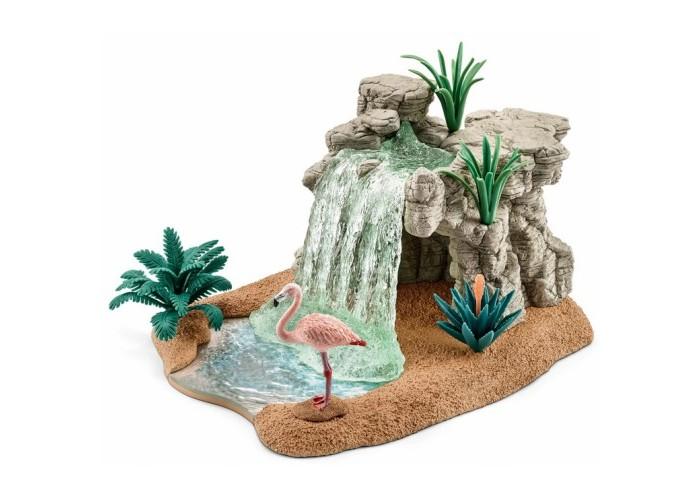 Schleich Игровой набор ВодопадИгровой набор ВодопадSchleich Игровой набор Водопад который произведет впечатление на каждого и ребенка и увлекающегося коллекционера.   Особенности: Фламинго предпочитают теплый климат и местность с большим количеством воды и мягкой почвы. Они обычно живут возле лагун и соленых озер, на болотах.  Крик чилийского фламинго похож на кряканье гуся.  Фламинго обнаружил прекрасное место возле водопада. Он останется там, пока вода остается теплой и соленой и пока рыба не съест всю его еду. Со своими длинными ногами фламинго может забраться глубже в воду, чем другие птицы, и, соответственно, найти больше еды. Как только он обнаружит лакомство, он наклоняет шею и погружает клюв в воду, чтобы поймать его. Затем он поднимает голову и заглатывает добычу. В комплекте: фрагмент водопада с растениями фигурка фламинго.<br>