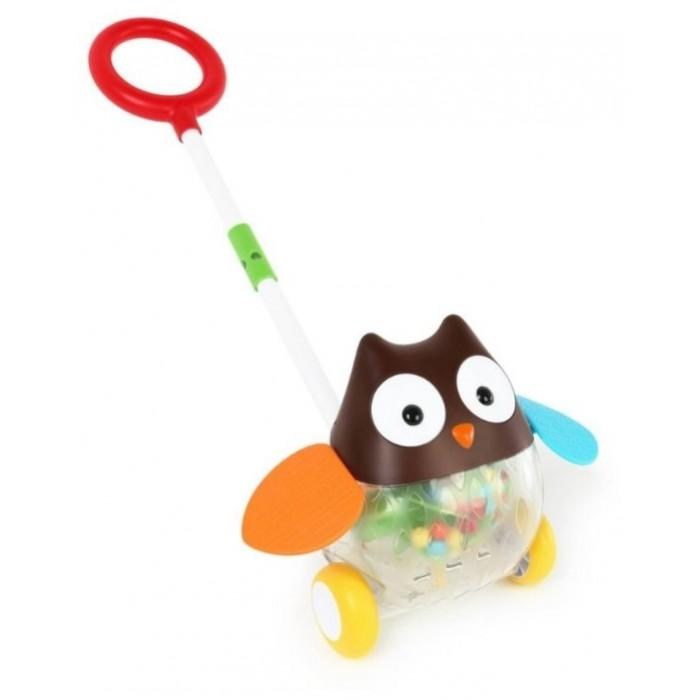 Каталка-игрушка Skip-Hop СоваСоваИгровая каталка с ручкой Skip-Hop Сова  предназначена для детей начинающих самостоятельно ходить. С ее помощью первые шаги малыша станут более уверенны, игрушка поддержит его при ходьбе.  Во время движения сова будет махать разноцветными, яркими крыльями. А в прозрачном животике совы будут кататься разноцветные шарики, издавая звук похожий на шум дождя.   Особенности:  Для удобства хранения у каталки съемная ручка.  Резиновые колеса смягчают движение игрушки и защищают пол от повреждений.  Материалы, использованные для оформления игрушки, являются нетоксичными.  Игрушка полностью безопасна для детей и не содержит фталатов.<br>
