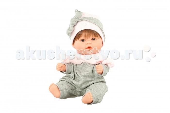 Dnenes/Carmen Gonzalez Бебетин в костюме с шапкой и шарфиком 21 смБебетин в костюме с шапкой и шарфиком 21 смОчень красивая кукла-пупс испанского производителя традиционных кукол для детей Dnenes. Высота куклы - 21 см.  Кукла выглядит очень нарядно и стильно в просторном сером трикотажном комбинезоне с манжетами на рукавах и брючках, воротником-стоечкой и застежкой - «липучкой» на спине.  На голове куклы одета шапочка из ярко-розового трикотажа с перфорированными сердечками. Оригинальность комплекту придают два шарфа из тех же тканей, что комбинезон и шапочка с узелками на концах — серый повязан на голову, а розовый на шее, но их вполне можно поменять местами.  Тело - Твердый винил Волосы - Темные, хорошо прошиты Глаза - Карие, стеклянные, без ресничек, не закрываются Одежда - Высококачественный текстиль. Серый трикотажный комбинезон Головной убор - Розовая трикотажная шапочка Детали - Два шарфа - розовый и серый Обувь - Нет Дизайн - Изысканный. Детали лица, рук и ножек великолепно проработаны.  Упаковка - Красивая подарочная коробка с прозрачным окошком.  Все куклы Carmen Gozalez производятся на заводе в Испании по классической технологии. Технология изготовления кукол из латекса или винила была внедрена в 1940 году, в 1950-х эта технология стала популярна среди известных кукольных брендов по всему миру. Все куклы изготавливаются по уникальным пресс-формам с применением ручного труда. Каждая кукла хранит в себе тепло рук мастера.  Компания Dnenes очень гордится качеством своих кукол, компания неоднократно получала престижные награды на международных выставках, имеет европейские сертификаты безопасности. К особенностям испанских кукол Carmen Gonzalez стоит отнести и тот факт, что куклы не имеют запаха, который многими производителями заглушается сильно пахнущими отдушками. Волосы у кукол имеют приятную фактуру, с большим вниманием дизайнеры отнеслись и к мелким деталям (ручки, ножки, пальчики) - все детали выполнены с великолепной точностью.<br>