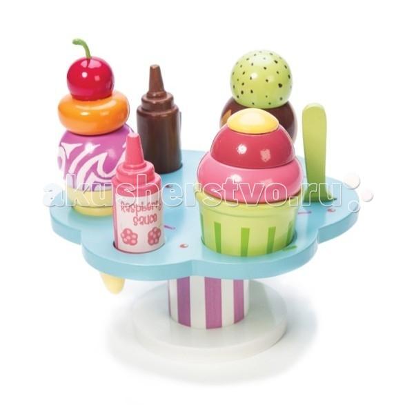 Деревянная игрушка LeToyVan Десерт-мороженое на подставкеДесерт-мороженое на подставкеНовое дополнение к коллекции Маленький повар - невероятно аппетитное мороженое на фигурной подставке.  Все элементы набора выполнены из дерева. Высота игрушки 15.5 см, диаметр - 16.7 см.  На фигурной подставке умещаются 3 порции разнообразного мороженого - фруктового, шоколадного, ягодного - в вафельном рожке и в стаканчике. К мороженому подается два сиропа - малиновый и шоколадный, а также ложечка для мороженого.   Игрушка упаковано в подарочную коробочку.  Игрушечная еда Десерт-мороженое на подставке: фигурная круглая подставка 3 мороженого, 2 сиропа, ложечка игрушка сделана из дерева яркая и привлекательная отличное дополнение к играм с едой и кухней подарочная упаковка<br>